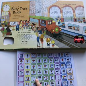 "picture of the first page of the ""Busy Train"" book and a core vocabulary communication board with a finger modeling/pointing to the word/symbol ""GO""."
