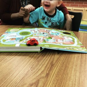 "picture of prek student reading and playing with the ""Busy Car"" book"