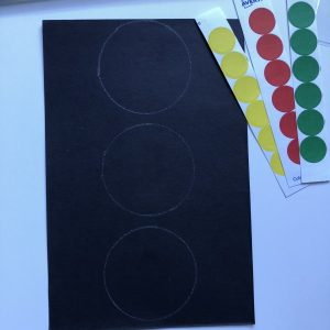 picture of black construction paper in a rectangle shape with 3 white circle outlines drawn down the middle of the paper and red, yellow and green circle stickers