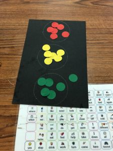 black construction paper rectangle with 3 white circles drawn down the center with red stickers in the top circle, yellow stickers in the middle and green stickers at the bottom